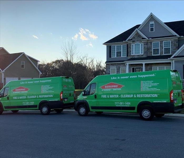 SERVPRO vans parked in front of a large home affected by water damage
