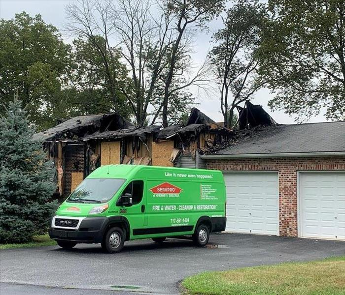 SERVPRO green van parked in front of a brick home damaged by a fire