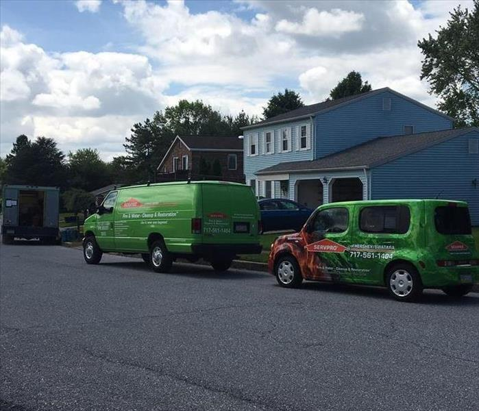 SERVPRO vehicles parked in front of a blue home affected by sewage damage