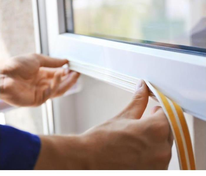 hands weather stripping a window
