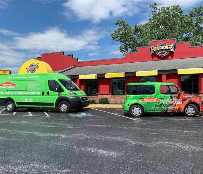 SERVPRO vehicles outside of a fudruckers water loss job